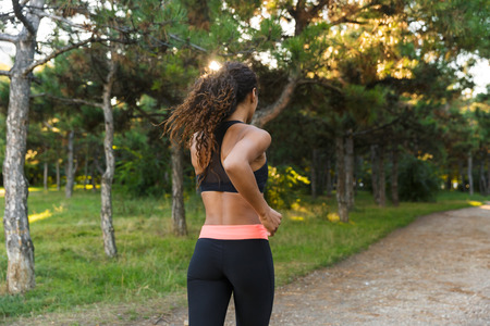 Brunette african american woman 20s wearing black tracksuit running through green park