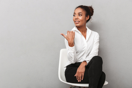 Attractive young african business woman wearing shirt sitting in a chair isolated over gray background, pointing away at copy space Imagens - 116704554