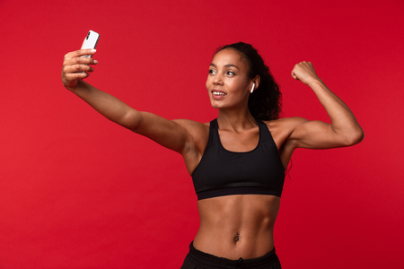 Image of a beautiful young african sports fitness woman posing isolated over red wall background listening music with earphones take a selfie by mobile phone showing biceps.