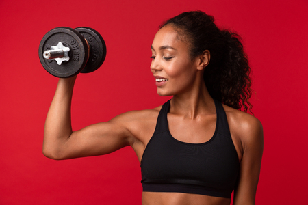 Image of beautiful african american woman in black sportswear lifting dumbbell isolated over red background Stock fotó