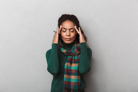 Desperate african woman wearing sweater standing over gray wall background, suffering from a strong migraine