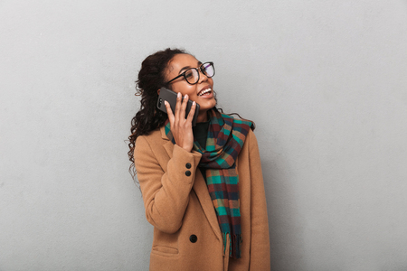 Smiling african woman wearing coat standing over gray background, talking on mobile phone
