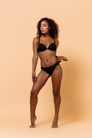 Beauty portrait of african american girl 20s wearing black lingerie standing isolated over beige background