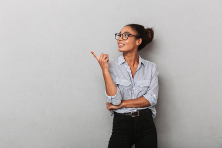 Confident african business woman wearing eyeglasses and shirt standing isolated over gray, pointing away