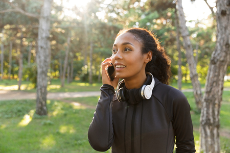 Image of cheerful woman 20s wearing black tracksuit and headphones using cell phone while walking through green park