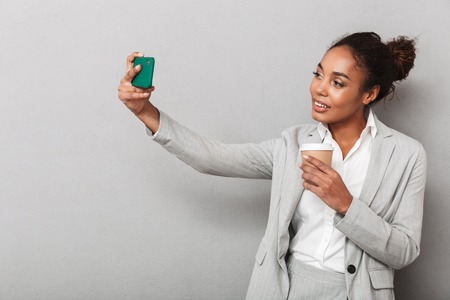 Attractive young african business woman standing isolated over gray background, holding cup of takeaway coffee, taking a selfie