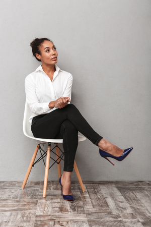 Attractive young african business woman wearing shirt sitting in a chair isolated over gray background, looking away at copy space Banco de Imagens
