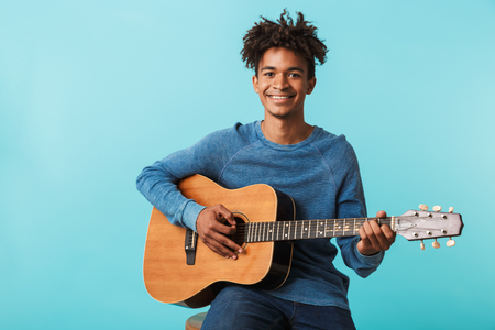Handsome young african man playing a guitar while sitting isolated over blue Imagens