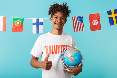 Portrait of a smiling young african man wearing voluteer t-shirt standing isolated over blue background, showing thumbs up