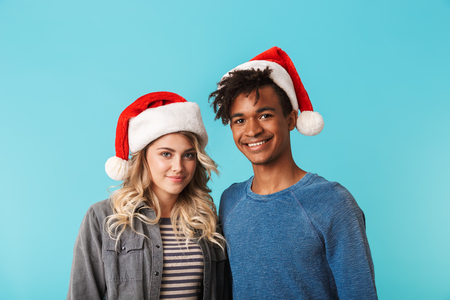 Happy multiracial young couple wearing christmas red hat isolated over blue background Stock Photo