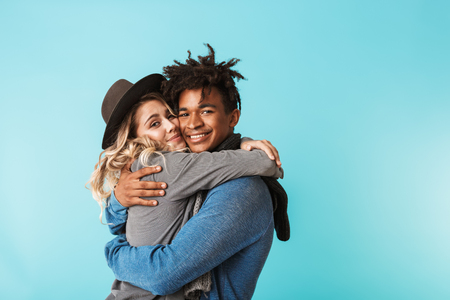 Smiling young multiracial couple wearing scarves standing isolated over blue background, hugging 写真素材