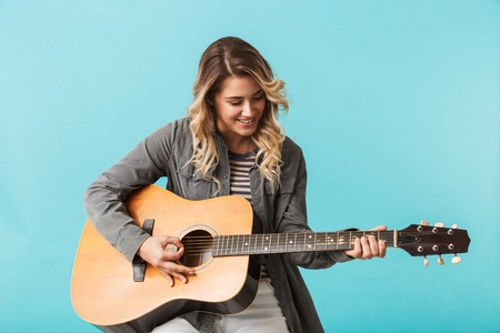 Smiling young girl playing a guitar while sitting isolated over blue Archivio Fotografico