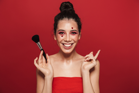 Beauty portrait of an attractive young topless woman wearing makeup standing isolated over red background, posing, holding a makeup brush Banque d'images - 116705891