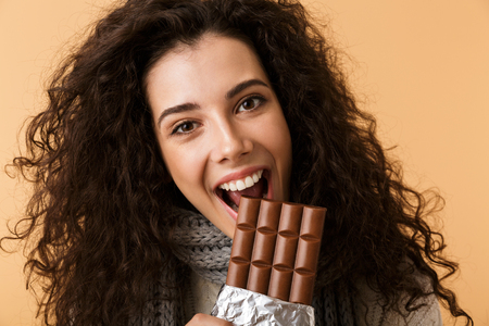 Cheerful young woman wearing sweater and scarf holding big chocolate bar isolated over beige background