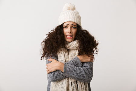 Upset young woman wearing winter scarf standing isolated over white background, shivering Stock Photo