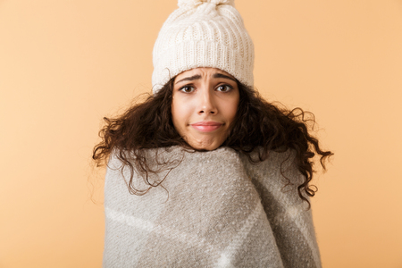 Upset young woman wearing winter scarf standing isolated over beige background, shivering Stock Photo