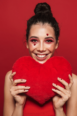 Beauty portrait of an attractive young woman wearing makeup standing isolated over red background, holding heart shaped pillow