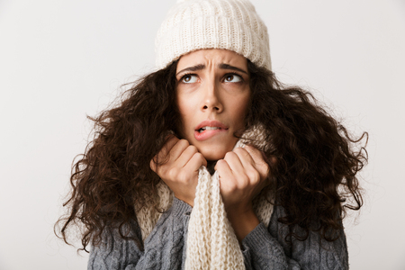 Upset young woman wearing winter scarf standing isolated over white background, shivering Фото со стока