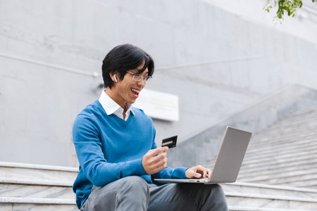 Smiling asian business man using laptop computer outdoors, showing credit card 스톡 콘텐츠