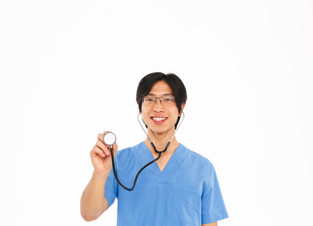 Confident asian man doctor wearing uniform and stethoscope standing isolated over white background Stock Photo