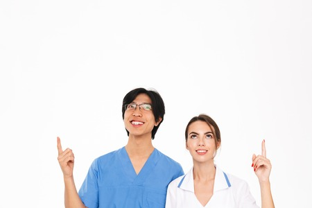 Smiling doctors couple wearing uniform standing isolated over white background, pointing at copy space Reklamní fotografie