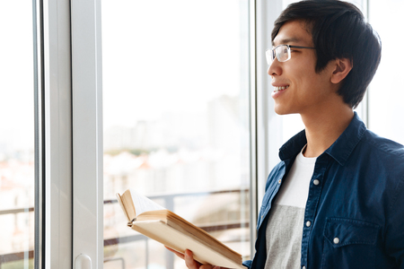 Smiling asian man reading a book while standing at the window at home