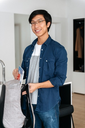 Smiling asian man packing his backpack, ready to leave apartment