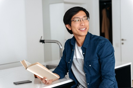Smiling asian man reading book while sitting on a kitchen at home