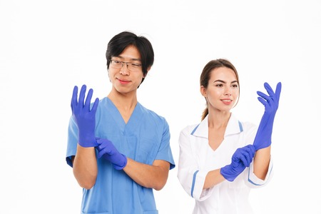 Smiling doctors couple wearing uniform and rubber gloves standing isolated over white background