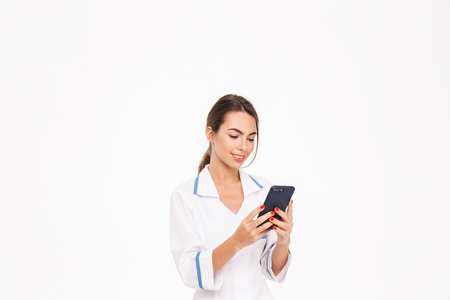 Confident young woman doctor wearing uniform standing isolated over white background, using mobile phone Stok Fotoğraf