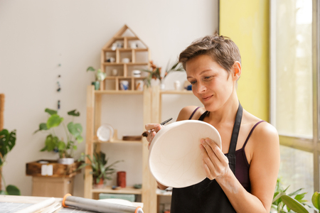 Young woman making ceramic and pottery tableware at the workshop