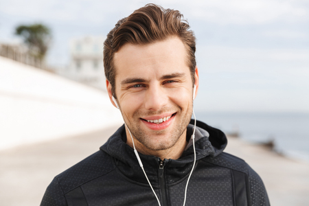 Image of sportive man 30s in black sportswear using earphones and mobile phone while walking along boardwalk at seaside