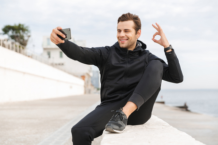 Image of athletic man 30s in black sportswear taking selfie photo on cell phone while sitting on boardwalk at seaside