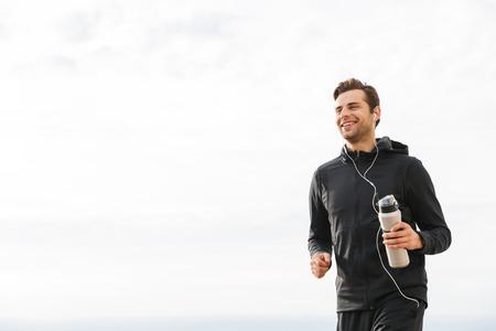 Imagen de deportista adulto de 30 años en ropa deportiva negra y auriculares haciendo ejercicio y corriendo junto al mar Foto de archivo