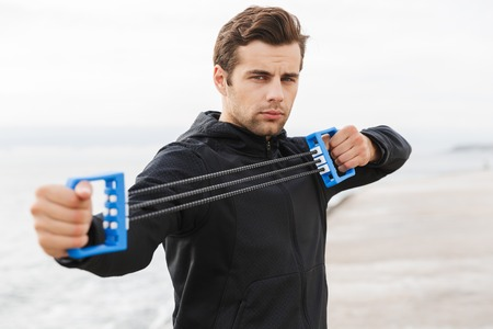 Handsome confident young sportsman working out at the beach, using chest expander