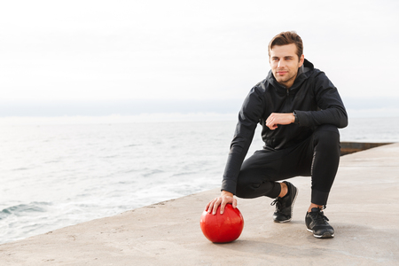 Handsome confident young sportsman working out at the beach, doing exercises with a heavy ball