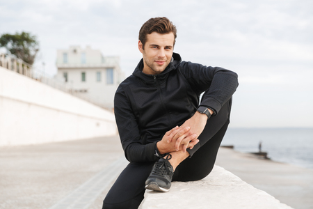 Image of sportive adult man 30s in black sportswear sitting on boardwalk at seaside Archivio Fotografico