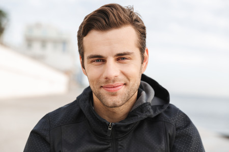 Image of handsome man 30s in black sportswear looking at camera while walking along boardwalk at seaside