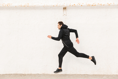 Image of caucasian man 30s in black sportswear and earphones running along white wall outdoor