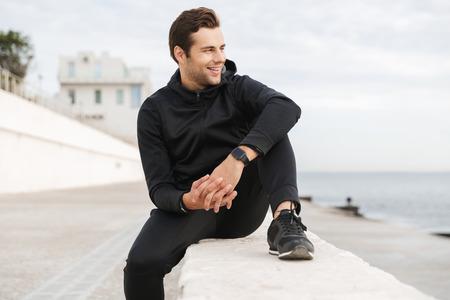 Image of athletic man 30s in black sportswear sitting on boardwalk at seaside