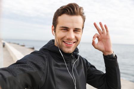 Bild eines zufriedenen Sportlers der 30er Jahre in schwarzer Sportbekleidung und Kopfhörern, der ein Selfie-Foto auf dem Handy macht, während er am Meer spazieren geht Standard-Bild