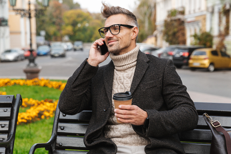 Handsome man wearing a coat sitting on a bench outdoors, talking on mobile phone, holding takeaway coffee cup Stock Photo