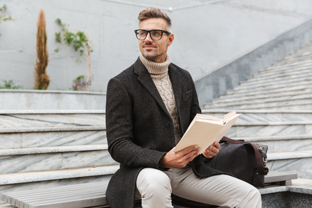 Handsome man wearing jacket reading a book while sitting outdoors 免版税图像 - 116484019