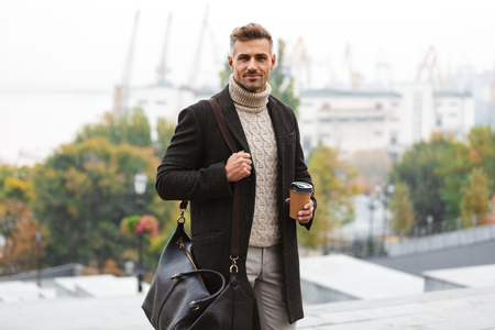 Foto eines kaukasischen glücklichen Mannes der 30er Jahre, der eine Jacke trägt, die Kaffee zum Mitnehmen hält, während er durch die Stadtstraße geht? Standard-Bild