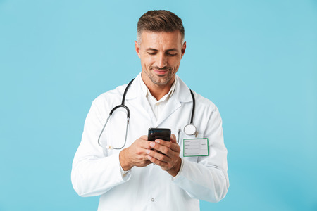 Photo of handsome medical doctor wearing white coat and stethoscope holding smartphone standing isolated over blue background