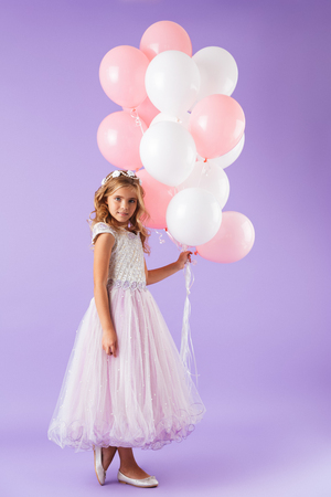 Full length of a pretty little girl dressed in princess dress standing isolated over violet background, holding bunch of balloons