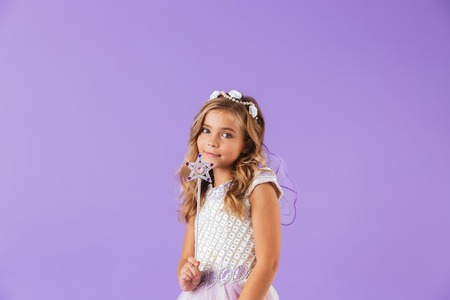 Portrait of a smiling cute pretty girl dressed in a princess dress isolated over violet background, holding magic wand Foto de archivo - 116483887