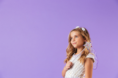 Portrait of a smiling cute pretty girl dressed in a princess dress isolated over violet background, holding magic wand, looking away
