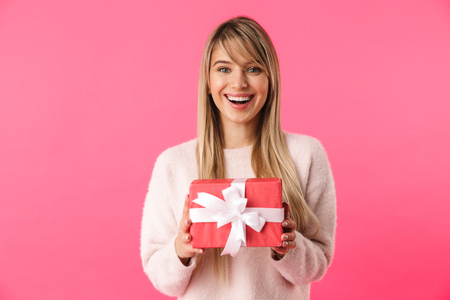 Cheerful young blonde girl standing isolated over pink background, showing gift box Foto de archivo