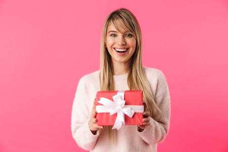 Fröhliches junges blondes Mädchen, das isoliert über rosafarbenem Hintergrund steht und Geschenkbox zeigt